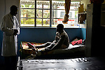Dr. Patric Irenge, Acting Director, talks to a man with a leg fracture in the surgery ward of Kibuye Hospital, Karongi District, Western Rwanda ..