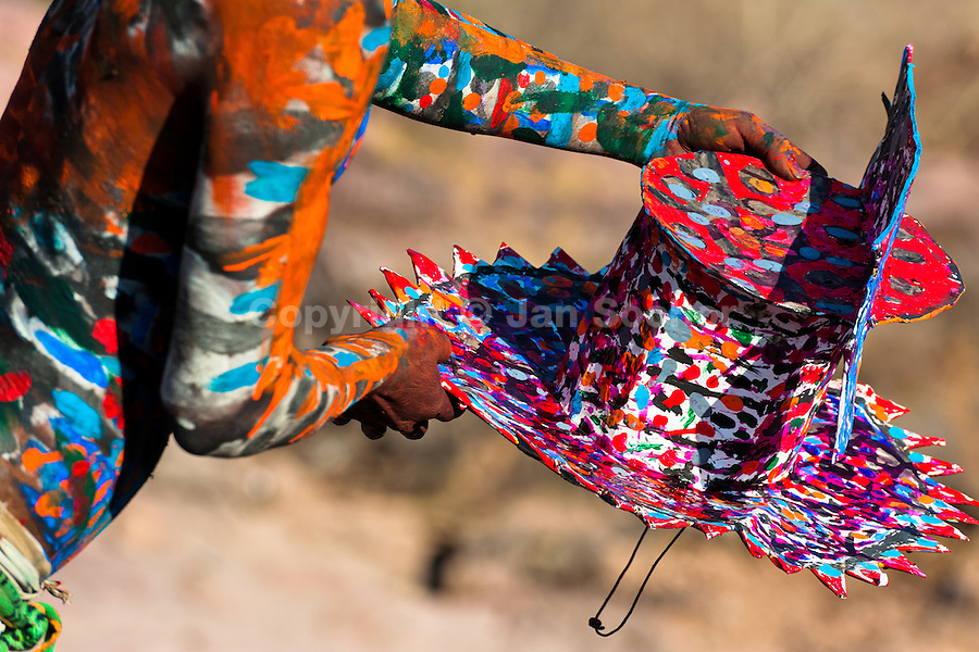 """A Cora Indian boy, with body painted colorfully, paints his multi-colored hat before the religious ritual ceremony of Semana Santa (Holy Week) in Jesús María, Nayarit, Mexico, 22 April 2011. The annual week-long Easter festivity (called """"La Judea""""), performed in the rugged mountain country of Sierra del Nayar, merges indigenous tradition (agricultural cycle and the regeneration of life worshipping) and animistic beliefs with the Christian dogma. Each year in the spring, the Cora villages are taken over by hundreds of wildly running men. Painted all over their semi-naked bodies, fighting ritual battles with wooden swords and dancing crazily, they perform demons (the evil) that metaphorically chase Jesus Christ, kill him, but finally fail due to his resurrection. La Judea, the Holy Week sacred spectacle, represents the most truthful expression of the Coras' culture, religiosity and identity."""