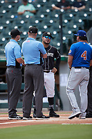 Charlotte Knights coach Daniel Gonzalez (26) meets with Durham Bulls manager Brady Williams (4) and umpires Ryan Wills, Jacob Metz, and Ben Sonntag prior to the game at Truist Field on August 28, 2021 in Charlotte, North Carolina. (Brian Westerholt/Four Seam Images)