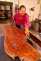 A man displays a large panel of native koa wood for furniture making.