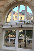 An artistic view of Place Dauphine, in the Ile de la Cité in Paris, with its garden and some typical buildings, through a reflected image on a mirror window.