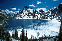 Sawtooth Lake and Mount Regan. Ice on high mountain lake basin, wilderness, mountains and forest landscape dusted with snow. Idaho, Sawtooth National Recreation Area.