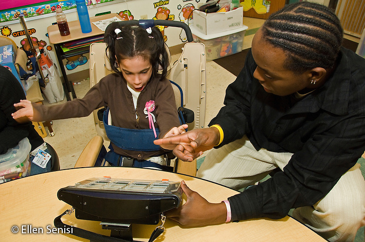MR / Albany, NY.Langan School at Center for Disability Services .Ungraded private school which serves individuals with multiple disabilities.Teaching assistant (African-American) helps a student use an alternative and augmentative communication device during speech and language development lesson. Girl: 7, cerebral palsy, nonverbal with expressive and receptive language delays..MR: Wes2, Del16.© Ellen B. Senisi