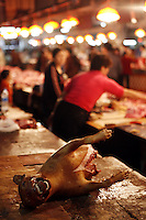 A half a German Shepherd dog lies on a counter at the Shenzhen Buji agriculture market.<br /> Shenzhen, China