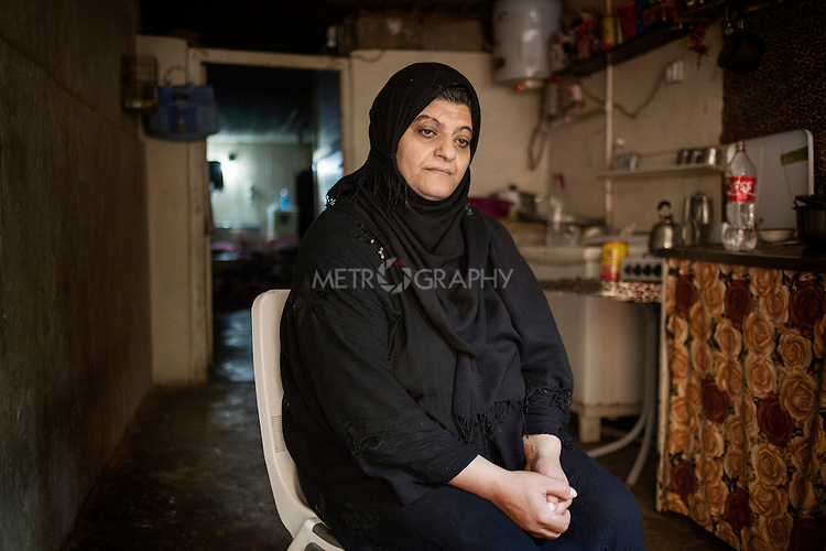 """29/08/15. Shaqlawa, Iraq. -- Sabah, 48 y.o. from Falluja inside her house, in the basement of a residential complex. Sabah left Falluja when the bakery of her son Omar was hit by a barrel bomb which killed him. She lives with her 4 children and pay 350.000 IQD for rent each month. He husband lives in Baharka camp, Erbil with his new wife, and only comes to Shaqlawa to freshen up when Erbil gets too hot. <br /> <br /> """"I could not sleep last night: I was thinking of the rent, and how to pay it. I sold all we had just to pay rent, but now we have nothing left""""."""