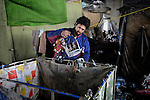 Arden Dasi, inspecting electronic equipment he collected in his recycling cart,  lived under a bridge in a Roma settlement in Belgrade, Serbia, when this photo was taken in February 2012. He is a refugee from Kosovo. The families that lived here, most of whom survive from recycling cardboard and other materials, were forcibly evicted in April 2012. Many were moved into metal shipping containers on the edge of Belgrade..