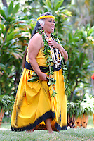Kumu, or teacher, of hula performs a chant at the Prince Lot Hula Festival in Moanalua Gardens on O'ahu. She wears lei of green maile leaves, black kukui nuts and shells.
