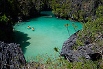 Tourists kayak inside the scenic Small Lagoon on Miniloc Island, near El Nido, in the famous and beautiful Bacuit Archipelago in Palawan, Philippines.