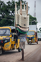"""Nigeria. Enugu State. Enugu. Town center. An Igbo young man carries a stack of plastic chairs on his head. He stands barefeet in the middle of the road. Traffic jam with auto rickshaw used by """"Keke"""" drivers for transporting people around town. The tricycle better known in Nigeria as the Keke NAPEP is gaining the dominance on Nigerian roads sweeping every street of cities and villages. The auto rickshaw is a common form of urban transport, both as a vehicle for hire and for private use. Enugu is the capital of Enugu State, located in southeastern Nigeria.  5.07.19 © 2019 Didier Ruef"""