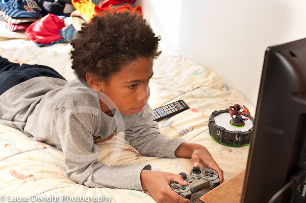 8 year old boy at home playing computer game