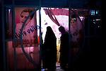 Baghdad, Iraq  : Sun 17th Oct 2010 :..Veiled women peel back the entrance to store selling revealing .wedding dresses on the streets of Sadr City. ..