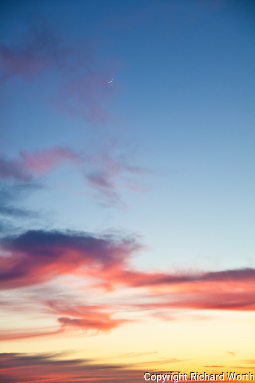A sliver of crescent moon looks down on an orange and red sunset at Bluff Top Coastal Park, Half Moon Bay, California.