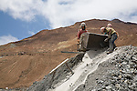 Miners dumping a load of ore from the mouth of a mine on the Cerro Rico.