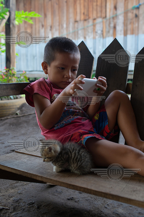 Elmer Garcia, 4, watches a video on his father's mobile phone outside his family's unit at the Single-Family Transitional Shelters.