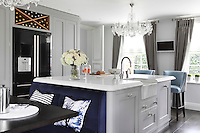 An informal dining area with a dark blue banquette sits next to the kitchen island which also acts as a breakfast bar and additional work surface