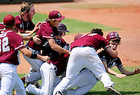 Mason City Newman's Riley Hanus, far right, is mobbed by jubilant teammates after scoring the winning run of an 11-1 five-inning victory over Lenox in the Class 1A championship game August 1, 2009 at Principal Park in Des Moines, Iowa.