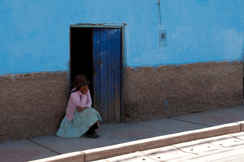 A young girl sits against a wall in Maras. The town of Maras area is not easily accessible; transportation to the town is limited to only a dirt paved road from Cusco and surrounding towns. Because of its well-known Salineras (Salt Works), Maras, a district of the Urubamba province, has become a popular tourist location.