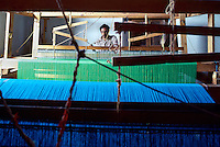Professional weaver works at large loom in his home-based shop. Patzcuaro, Michoacan, Mexico.