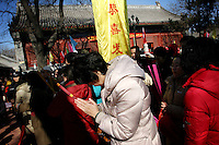 CHINA. A woman praying during Chinese New Year in Baiyun Temple in Beijing.  Chinese New Year, or Spring Festival, is the most important festival and holiday in the Chinese calendar In mainland China, many people use this holiday to visit family and friends and also visit local temples to offer prayers to their ancestors. The roots of Chinese New Year lie in combined influences from Buddhism, Taoism, Confucianism, and folk religions.  2008.