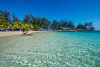 Honduras, Roatan Island, Fantasy Island Resort, Caribbean. Woman in lounge chair reading a maagzine.