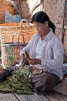 Myanmar, Burma.  Burmese Woman of Intha Ethnic Group Making Cheroots, Inle Lake, Shan State.  Corn husks are used as filters, cordia dichotoma leaves used to wrap the tobacco.