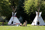 A Native American Indian tipi campsite with men playing the drum and flute