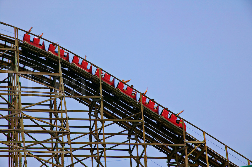 Red roller coaster on tracks against blue sky