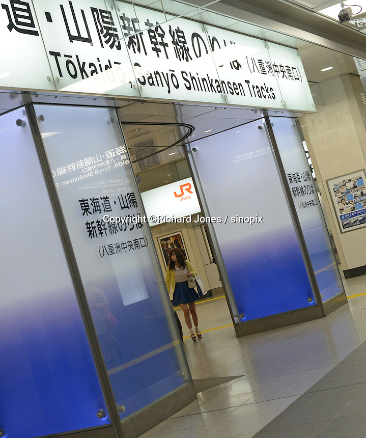 Young woman walks through the Tokaido and Sanyo Shinkansen entrance at Tokyo Station.