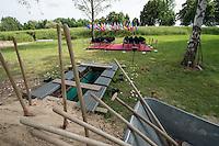 """Das """"Zentrum fuer Politische Schoenheit"""" liess am Dienstag den 16. Juni 2015 auf dem Muslimischen Teil des Friedhof in Berlin-Gatow eine Fluechtlingsfrau aus Syrien beerdigen, die mit ihrem Kind bei der Flucht ueber das Mittelmeer ertrunken ist. Ihr Kind konnte nicht geborgen werden, es ist im Mittelmeer verschollen.<br /> Die Frau wurde zuvor im Beisein von Angehoerigen in Suedeuropa exhumiert und durch ein Beerdigungsunternehmen nach Deutschland gebracht. Die Beerdigung fand unter dem Motto """"Die Toten kommen"""" statt und war die erste von insgesammt 10 geplanten Beerdigungen.<br /> Vor dem Grab waren 40 Stuehle fuer eingeladene Beerdigungs-Gaeste aufgestellt die jedoch leer blieben. Es waren die politisch Verantwortlichen der deutschen Asylpolitik geladen worden, die jedoch nicht erschienen.<br /> Das Zentrum fuer Politische Schoenheit will 8 weitere Mittelmeer-Tote nach Berlin bringen und sie vor das Kanzleramt bringen um den politisch Verantwortlichen die Folgen ihrer Asylpolitik drastisch vor Augen zu fuehren.<br /> Im Bild: Das offene Grab und die leeren Stuehle der geladenen Gaeste. Dahinter die Landesflaggen der Europaeischen Mitgliedsstaaten.<br /> 16.6.2015, Berlin<br /> Copyright: Christian-Ditsch.de<br /> [Inhaltsveraendernde Manipulation des Fotos nur nach ausdruecklicher Genehmigung des Fotografen. Vereinbarungen ueber Abtretung von Persoenlichkeitsrechten/Model Release der abgebildeten Person/Personen liegen nicht vor. NO MODEL RELEASE! Nur fuer Redaktionelle Zwecke. Don't publish without copyright Christian-Ditsch.de, Veroeffentlichung nur mit Fotografennennung, sowie gegen Honorar, MwSt. und Beleg. Konto: I N G - D i B a, IBAN DE58500105175400192269, BIC INGDDEFFXXX, Kontakt: post@christian-ditsch.de<br /> Bei der Bearbeitung der Dateiinformationen darf die Urheberkennzeichnung in den EXIF- und  IPTC-Daten nicht entfernt werden, diese sind in digitalen Medien nach §95c UrhG rechtlich geschuetzt. Der Urhebervermerk wird gemaess §13 UrhG verlangt.]"""