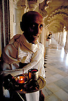 Smiling Monk carries a brass tray with candles at Jain Temple in Ahmadabad, India. Ahmadabad is the capital of the Gujarat state, NW India, on the Sabarmati River. Ahmadabad, India.