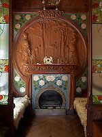 Gaspar Homar designed the furniture, which was made especially for the house, in the Art Nouveau style. Benches covered in sheepskin flank a mosaic tiled fireplace with a carved wood over-mantel in this small snug