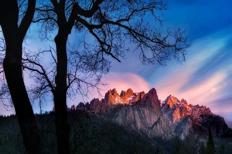 Castle Craigs breaking thriugh clouds with sunrise. Castle Craigs State Park, CA