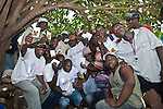 After an HIV/AIDS educational session organized by PSI-Guinea, members of the crowd hold up samples of Prudence Plus brand condoms.