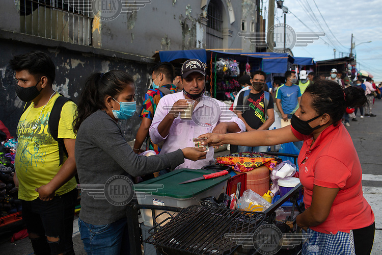 Marta Gomez (right), 26, sells sandwiches and drinks to people waiting in line hoping to acquire a copy of their criminal records, a normal requirement for job applications in Guatemala. Some of the people arrived at four in the morning, three hours before the police station opens, and expect to be attended sometime before noon. Marta used to sell in the bus terminal, but since all public transport has been cancelled since 13 March 2020 due to the COVID-19 pandemic, she spends her mornings in this area near the police station.