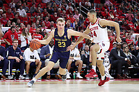 RALEIGH, NC - JANUARY 9: Dane Goodwin #23 of the University of Notre Dame drives past Jericole Hellems #4 of North Carolina State University during a game between Notre Dame and NC State at PNC Arena on January 9, 2020 in Raleigh, North Carolina.
