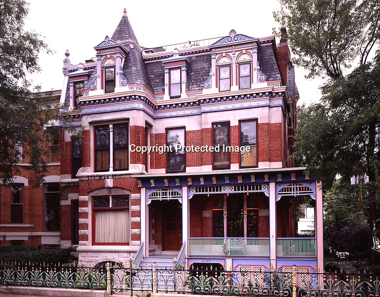 Three-story Victorian style , red brick siding, and an intricate fence