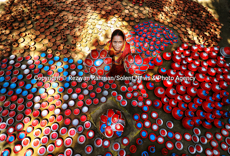 Pictured: A woman is surrounded by thousands of brightly coloured clay pots as they are made for a religious festival in Gaibandha, Bangladesh.<br /> <br /> Each individual clay pot is designed by hand, and are used as kitchenware as well as toys for children whilst the adults are cooking.<br /> <br /> The photographs were taken by 26 year old freelance photographer Rezwan Rahman. <br /> <br /> Over 1000 clay pots and toys were made for the hindu festival Durga Puja, which runs until December 26, 2020. <br /> <br /> Please byline: Rezwan Rahman/Solent News<br /> <br /> © Rezwan Rahman/Solent News & Photo Agency<br /> UK +44 (0) 2380 458800