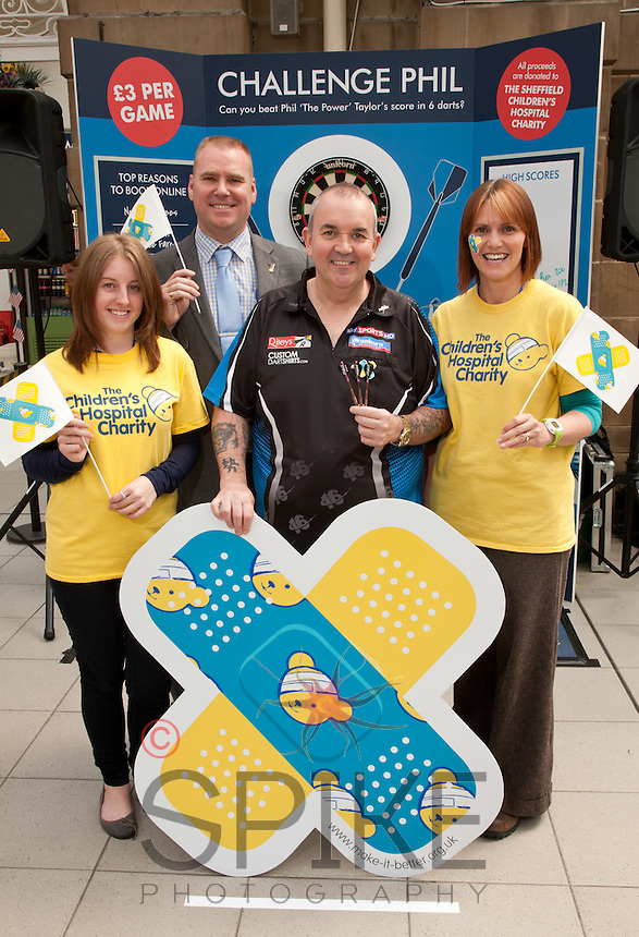 Phil 'The Power' Taylor raised money for The Children's Hospital Charity by challenging the public at darts at Sheffield Train Station Here Phil is pictured with Rebecca Lawson (left) and Tonya Kennedy of The Childrens Hospital Charity and Jason Cocker, Sheffield Train Station manager