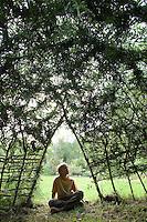 Hütte, Tipi aus Weidenzweigen, Weidenstecklingen im Garten, Zweige von Weide wurden in die Erde gesteckt und sind angewachsen und wurden zu einer Hütte geformt und verflochten, Kind, Junge sitzt am Eingang und schnitzt mit Schnitzmesser, Kopfweide, Kopfweiden, Kopf-Weide, Salix spec., Weidentipi, Weidenhütte