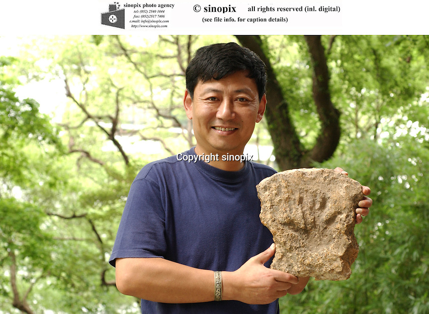 PROFESSOR DAVID ZHANG: HKU: HONG KONG UNIVERSITY: HONG KONG <br /> Professor Daivd Zhang of The Hong Kong University holds up a rock containing the imprint of a hand. He found 19 handprints and footprints and believes they could have been made deliberately in mud deposits by people living near hot springs.<br /> Photo by Richard Jones/sinopix<br /> ©sinopix<br /> <br /> MEDICAL/MEDICINE