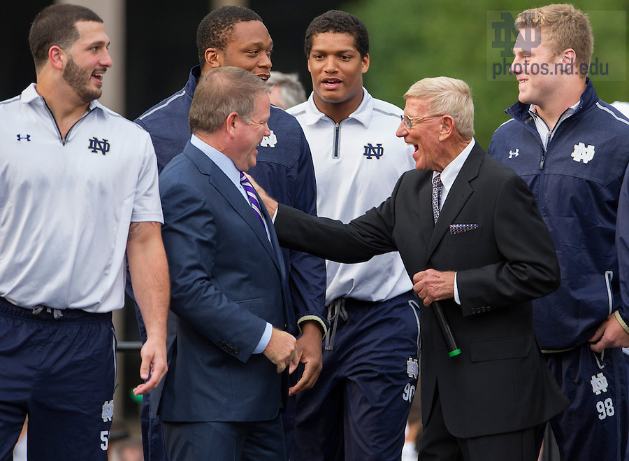 Sept. 5, 2014; Head football coach Brian Kelly and former coach Lou Holtz share a laugh on stage during the pep rally before the game against Michigan. (Photo by Barbara Johnston/ University of Notre Dame)
