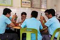 Young Malaysian Men Meeting for Lunch, with Cell Phones, Taiping, Malaysia.