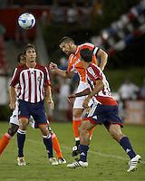 Houston Dynamo defender Wade Barrett heads the ball away from Chivas USA forward Ante Razov (l) and Chivas USA midfielder Juan Pablo Garcia (r).  Houston Dynamo and Chivas USA drew to a 0-0 tie at Robertson Stadium in Houston, TX on September 17, 2006.