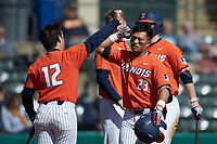 Branden Comia (23) of the Illinois Fighting Illini bumps forearms with teammate Brody Harding (12) after hitting a two-run home run against the West Virginia Mountaineers at TicketReturn.com Field at Pelicans Ballpark on February 23, 2020 in Myrtle Beach, South Carolina. The Fighting Illini defeated the Mountaineers 2-1.  (Brian Westerholt/Four Seam Images)