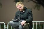 """© Joel Goodman - 07973 332324 . 03/11/2017 . Manchester , UK . A man reads a copy of Tommy Robinson's (real name Stephen Yaxley-Lennon ) book at the launch of the former EDL leader's book """" Mohammed's Koran """" at Castlefield Bowl . Originally planned as a ticket-only event at Bowlers Exhibition Centre , the launch was moved at short notice to a public location in the city . Photo credit : Joel Goodman"""
