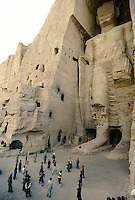 A volleyball match between Hazara Mujahedin team's at the foot of the Bamiyan Buddha of 54 meters high, in 1995..These magnificent colossal statues, created during the 3rdâ4th centuries A.D., attracted pilgrims for centuries, far beyond the time when Buddhism languished in India following the disastrous visitation of the Hephthalite Huns in the 5th century, the subsequent resurgence of Hinduism, and the arrival of iconoclastic Islam in the 7th century..The entire niche was once covered with paintings dating from i he late 5th to the early 7th centuries.