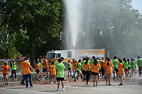 Firefighters with Springdale Fire Department spray water Thursday, Sept. 9, 2021, to clean the parking lot and the students during the Tomatina, a tomato fight with historical roots in Spain, in Murphy Park in Springdale. Advanced placement Spanish language students from Springdale and Har-Ber high schools participated in the event. Visit nwaonline.com/210910Daily/ for today's photo gallery.<br /> (NWA Democrat-Gazette/Andy Shupe)