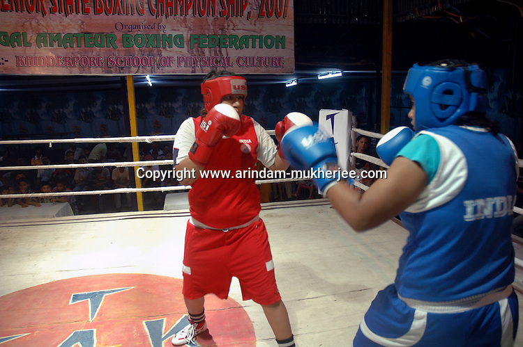 INDIA (West Bengal - Calcutta)August 2007,Shakila Babe (left) fights with Sanno Babe (right) at the finals of a championship  in Kolkata. Shakila and Shanno are twins from a poor muslim family of Iqbalpur, Kolkata. . Inspite of their late father's unwillingness to send his daughters to take up  boxing her mother Banno Begum inspired them to take up boxing at the age of 3. Their father was more concerned about the social stigma they have in their community regarding women coming into sports or doing anything which may show disrespect to the religious emotions of his community. Shakila now has been recognised as one of the best young woman boxers of the country after she won the  international championship at Turkey in the junior category. Shanno is also been called for the National camp this year. Presently Shakila and shanno has become the role model in the Iqbalpur area  and parents from muslim community of Iqbalpur have started showing interst in boxing. Iqbalpur is a poor muslim dominated area mostly covered with shanty town with all odds which comes along with poverty and lack of education. - Arindam Mukherjee