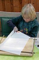 Kinder basteln ein Fensterbild mit Blüten, Junge schneidet Pergamentpapier in die richtige Größe
