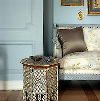An antique inlaid table has been placed next to the Empire-style sofa creating a subtly rich effect in the living room of a New York apartment